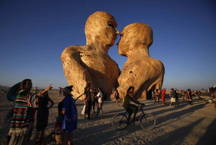 "People gather around the art installation Embrace during the Burning Man 2014 ""Caravansary"" arts and music festival in the Black Rock Desert of Nevada August 26, 2014. People from all over the world have gathered at the sold out festival to spend a week in the remote desert cut off from much of the outside world to experience art, music and the unique community that develops. Picture taken August 26, 2014. (Jim Urquhart/Reuters)"