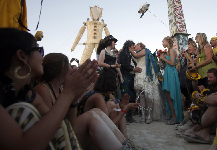 "Andrew Johnstone (standing, 2nd L), the designer of this year's man structure, marries Jeri Schneider during a ceremony at the Burning Man 2014 ""Caravansary"" arts and music festival in the Black Rock Desert of Nevada, August 27, 2014. People from all over the world have gathered at the sold out festival to spend a week in the remote desert cut off from much of the outside world to experience art, music and the unique community that develops. (Jim Urquhart/Reuters)"