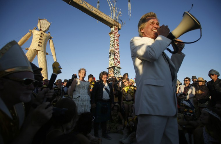"Andrew Johnstone (C), the designer of this year's man, marries Jeri Schneider (standing L) during a ceremony officiated by Reverend Billy of the Church of Stop Shopping (front R) during the Burning Man 2014 ""Caravansary"" arts and music festival in the Black Rock Desert of Nevada, August 27, 2014. People from all over the world have gathered at the sold out festival to spend a week in the remote desert cut off from much of the outside world to experience art, music and the unique community that develops. (Jim Urquhart/Reuters)"