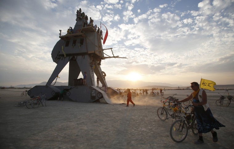 "Participants interact with the Alien Siege Machine during the Burning Man 2014 ""Caravansary"" arts and music festival in the Black Rock Desert of Nevada, August 28, 2014. (Jim Urquhart/Reuters)"