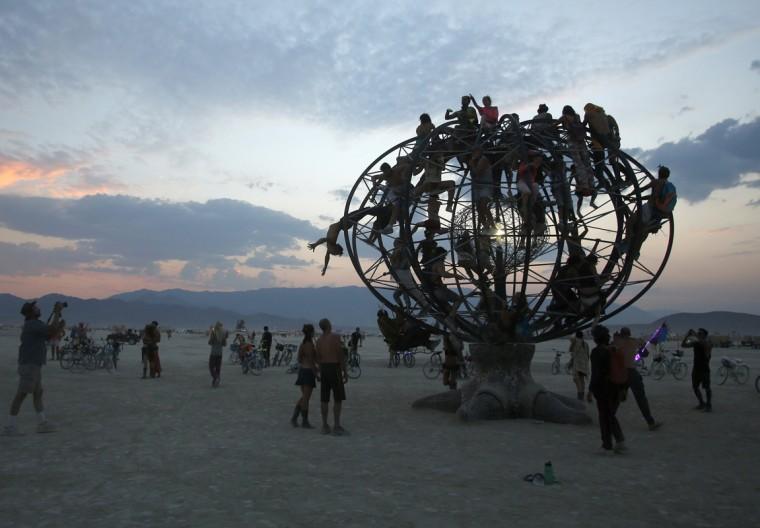 "Participants climb an the Eidolon Panspermia Ostentatia Duodenum (EPOD) art installation during the Burning Man 2014 ""Caravansary"" arts and music festival in the Black Rock Desert of Nevada, August 28, 2014. (Jim Urquhart/Reuters)"