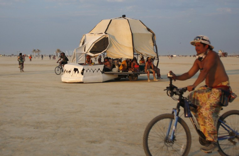 """A mutant vehicle drives across the Playa during the Burning Man 2014 """"Caravansary"""" arts and music festival in the Black Rock Desert of Nevada, August 28, 2014. (Jim Urquhart/Reuters)"""
