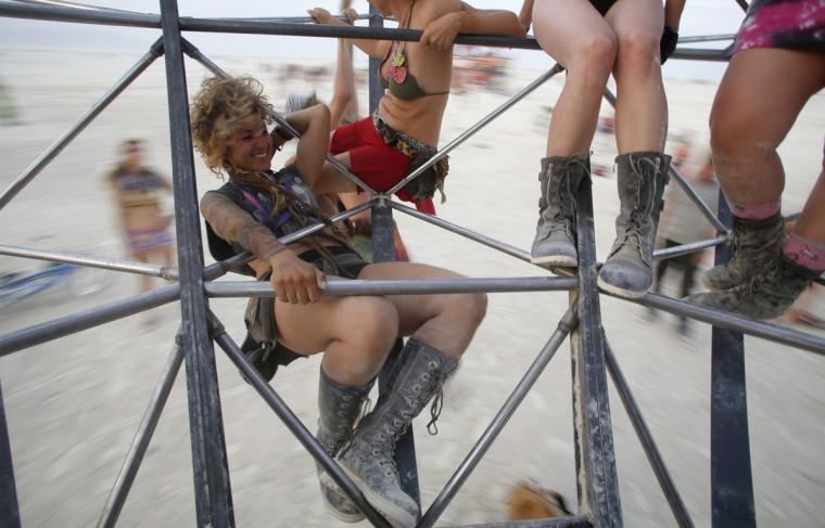 "Elesa Rouel rides on the Eidolon Panspermia Ostentatia Duodenum (EPOD) art installation during the Burning Man 2014 ""Caravansary"" arts and music festival in the Black Rock Desert of Nevada, August 28, 2014. (Jim Urquhart/Reuters)"