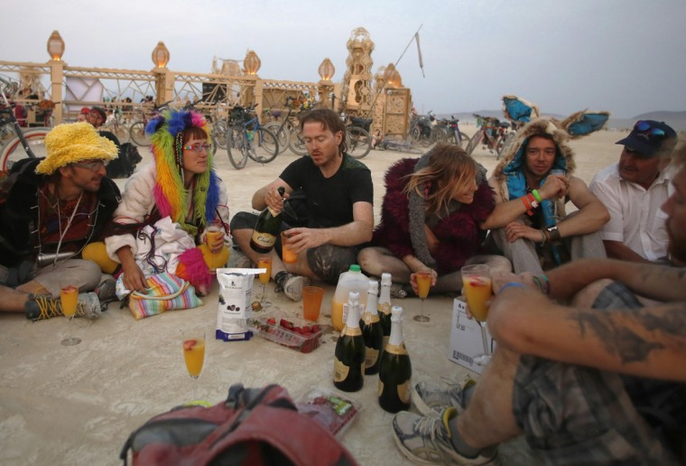"Participants enjoy drinks before sunrise at the Temple of Grace during the Burning Man 2014 ""Caravansary"" arts and music festival in the Black Rock Desert of Nevada, August 29, 2014. People from all over the world have gathered at the sold out festival to spend a week in the remote desert cut off from much of the outside world to experience art, music and the unique community that develops. (Jim Urquhart/Reuters)"