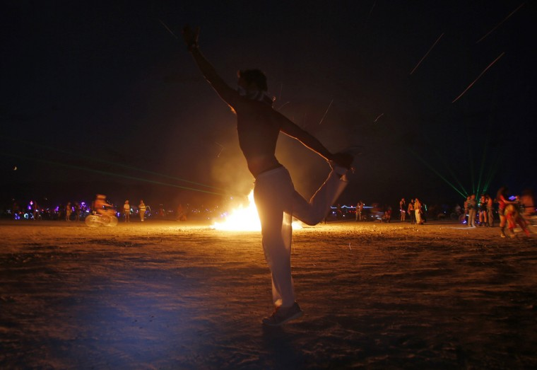 "Omri Cohen dances around a burning art installation during the Burning Man 2014 ""Caravansary"" arts and music festival in the Black Rock Desert of Nevada, August 28, 2014. People from all over the world have gathered at the sold out festival to spend a week in the remote desert cut off from much of the outside world to experience art, music and the unique community that develops. Picture taken August 28, 2014. (Jim Urquhart/Reuters)"