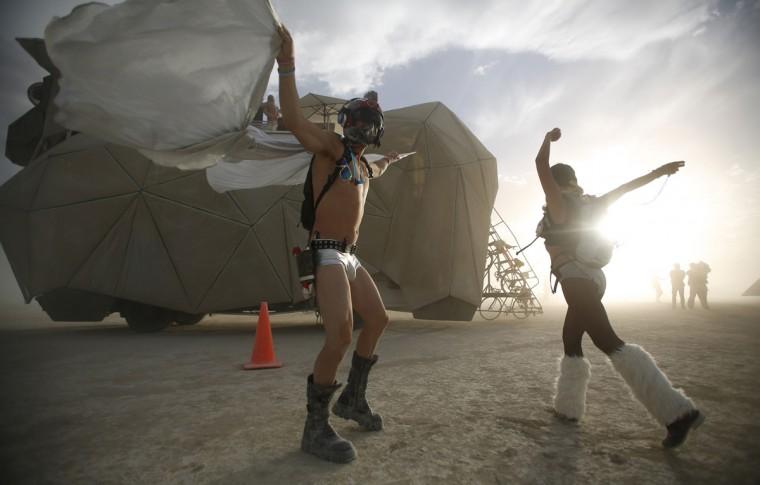 "Dillon Bracken (L) and Atalya Stachel dance during the Burning Man 2014 ""Caravansary"" arts and music festival in the Black Rock Desert of Nevada, August 30, 2014. (Jim Urquhart/Reuters)"