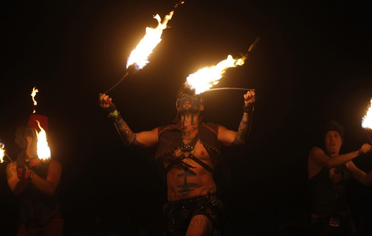 "Members of the Kenna Tribe fire conclave perform before the Man burns during the Burning Man 2014 ""Caravansary"" arts and music festival in the Black Rock Desert of Nevada, August 30, 2014. (Jim Urquhart/Reuters)"