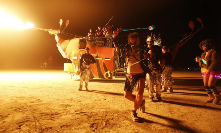 "Grayson Hawe dances in front of a mutant vehicle during the Burning Man 2014 ""Caravansary"" arts and music festival in the Black Rock Desert of Nevada, August 29, 2014. (Jim Urquhart/Reuters)"
