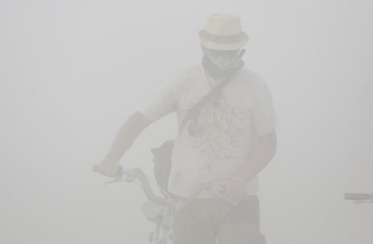 "Christoffer McCollom navigates a dust storm during the Burning Man 2014 ""Caravansary"" arts and music festival in the Black Rock Desert of Nevada, August 29, 2014. (Jim Urquhart/Reuters)"