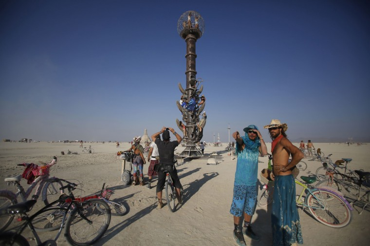 "Participants climb the Minaret art installation on the last day of the Burning Man 2014 ""Caravansary"" arts and music festival in the Black Rock Desert of Nevada, August 31, 2014. (Jim Urquhart/Reuters)"