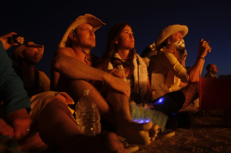 "Josh Moore (L) and Danille Finnerman watch as the Temple of Grace burns on the last day of the Burning Man 2014 ""Caravansary"" arts and music festival in the Black Rock Desert of Nevada, August 31, 2014. (Jim Urquhart/Reuters)"