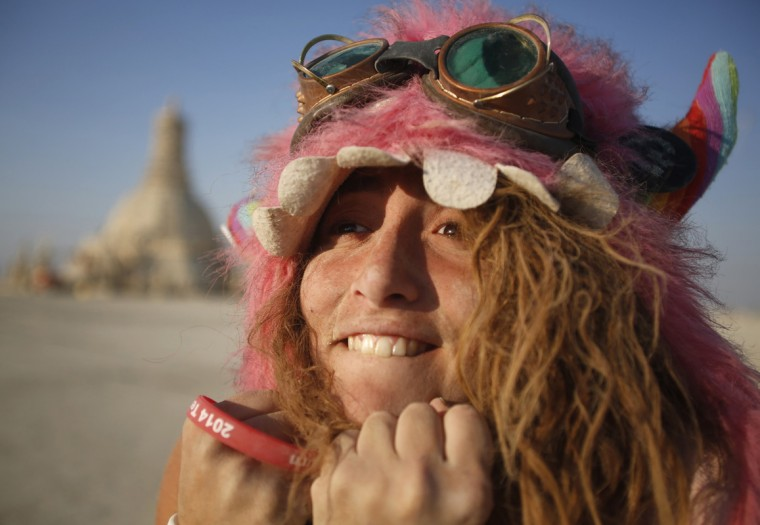 "Participant Sandy Candy smiles before the Temple of Grace burns on the last day of the Burning Man 2014 ""Caravansary"" arts and music festival in the Black Rock Desert of Nevada, August 31, 2014. Over 65,000 people from all over the world have gathered at the sold out festival to spend a week in the remote desert cut off from much of the outside world to experience art, music and the unique community that develops. (Jim Urquhart/Reuters)"