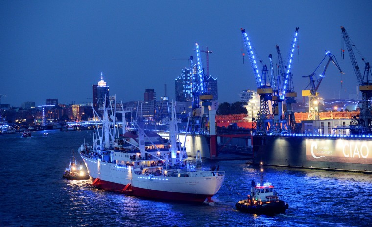 "The museum vessel ""Cap San Diego"" passes by the illuminated harbour of Hamburg, northern Germany on the first day of the ""Hamburg Cruise Days"". Six cruise liner are expected during the event that takes place from August 1 to 3, 2014. (Daniel Reinhardt/AFP-Getty Images)"