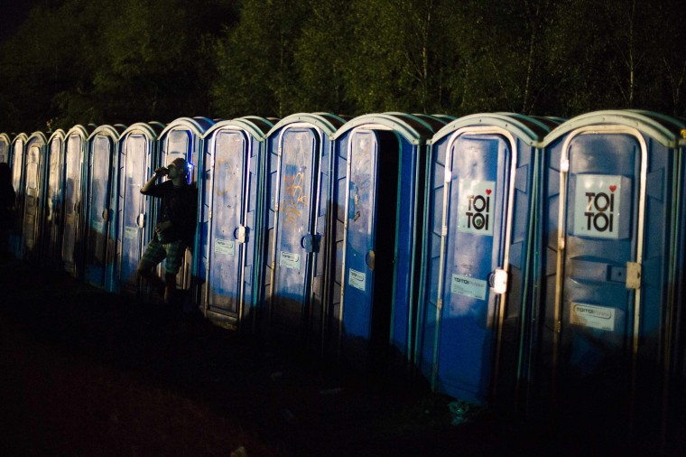 A man leans against a portable toilet at the Woodstock Festival in Kostrzyn-upon-Odra, close to the Polish-German border. Some 500,000 people attended the festival that is the brainchild of Polish journalist and social campaigner Jerzy Owsiak. He initiated the event to say thank you to those who donated money to his GOCC charity organisation that delivers medical care for children. (Thomas Peter/Reuters)