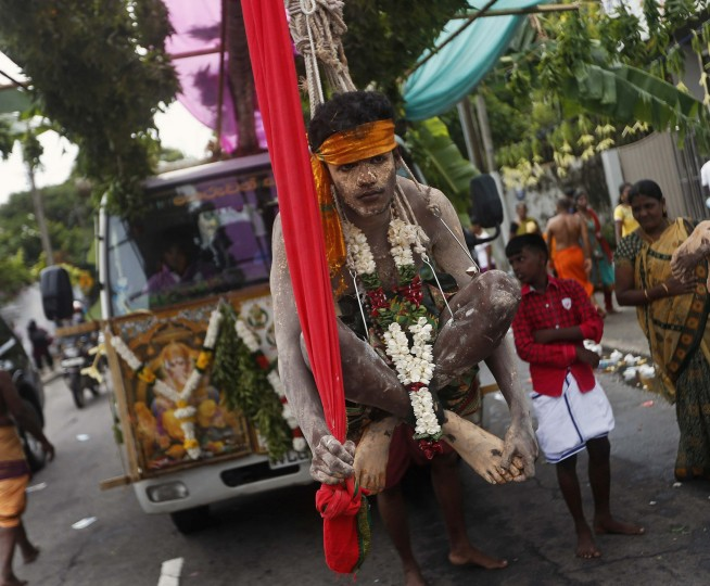 A devotee hangs from a wooden pole with hooks attached during the annual Chariot festival of the Sri Mayurapathy Paththirakaali temple in Colombo. The chariot procession starts at the temple and is brought through streets as Hindu devotees follow behind, performing acts of penance or thanksgiving such as piercing hooks through their skin, in order to fulfill their vows to the Hindu gods. (Dinuka Liyanawatte/Reuters)