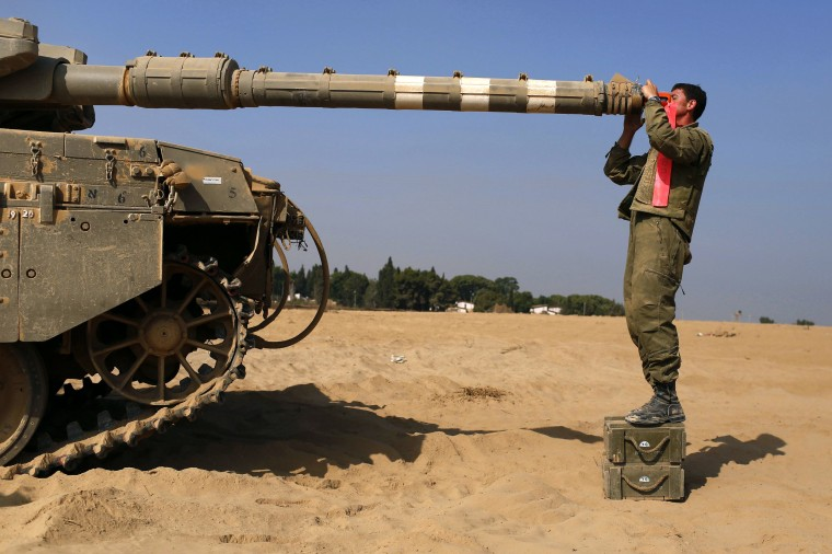 An Israeli soldier inspects a tank near the border with Gaza. Hamas claimed responsibility on Saturday for a deadly Gaza Strip ambush in which an Israeli army officer may have been captured, but said the incident likely preceded and therefore had not violated a U.S.- and U.N.-sponsored truce. Palestinian officials say 1,650 Gazans, most of them civilians, have been killed, including a muezzin who died in an Israeli strike on a northern mosque on Saturday. Sixty-three Israeli soldiers have been killed, and Palestinian shelling has killed three civilians in Israel. Israel launched a Gaza air and naval offensive on July 8 following a surge of cross-border rocket salvoes by Hamas and other Palestinian guerrillas, later escalating into ground incursions centred along the tunnel-riddled eastern frontier of the enclave but often pushing into residential areas. (Siegfried Modola/Reuters)