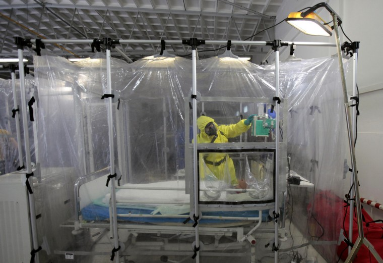 A Czech military personnel wearing protective gear takes part in a drill with a dummy in the Biological Defence Centre, a specialised medical institution ensuring complete biological defence, in the village of Techonin August 11, 2014. The Biological Defence Department is involved in the NATO biological defence system and is equipped for treatment of possible Ebola virus patients. (David W Cerny/Reuters)