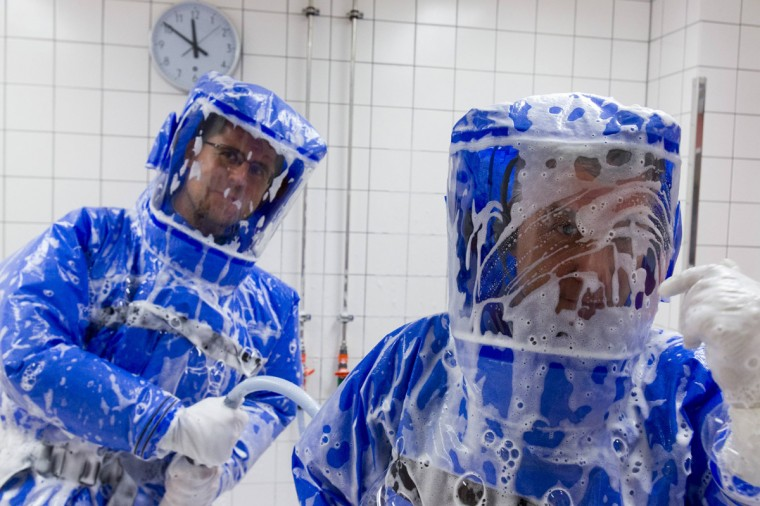 Doctor for tropical medicine Florian Steiner (R) and ward physician Thomas Klotzkowski stand in a disinfection chamber after cleaning their protective suits at the quarantine station for patients with infectious diseases at the Charite hospital in Berlin August 11, 2014. (Thomas Peter/Reuters)