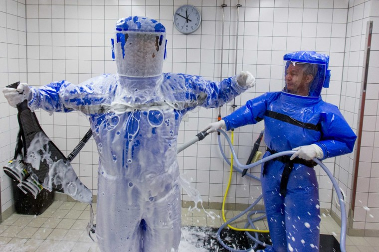 Ward physician Thomas Klotzkowski (R) cleans doctor for tropical medicine, Florian Steiner, in a disinfection chamber at the quarantine station for patients with infectious diseases at the Charite hospital in Berlin August 11, 2014. (Thomas Peter/Reuters)