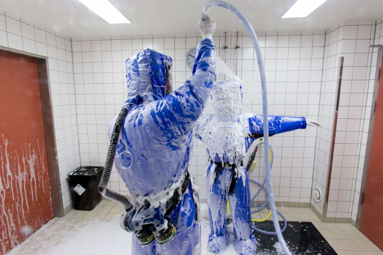 Doctor for tropical medicine Florian Steiner (L) cleans ward physician Thomas Klotzkowski in a disinfection chamber at the quarantine station for patients with infectious diseases at the Charite hospital in Berlin August 11, 2014. (Thomas Peter/Reuters)