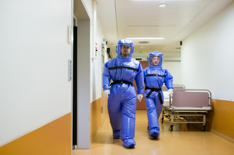 Ward physician Thomas Klotzkowski and doctor for tropical medicine Florian Steiner (L) wear protective suits as they walk in the quarantine station for patients with infectious diseases at the Charite hospital in Berlin August 11, 2014. The isolation ward at the Charite is one of several centres in Germany equipped to treat patients suffering from ebola and other highly infectious diseases, the clinic's doctor for tropical medicine Florian Steiner said. Ebola is one of the deadliest diseases known to humanity. It has no proven cure and there is no vaccine to prevent infection. The most effective treatment involves alleviating symptoms that include fever, vomiting and diarrhoea. The rigorous use of quarantine is needed to prevent its spread, as well as high standards of hygiene for anyone who might come into contact with the disease. (Thomas Peter/Reuters)