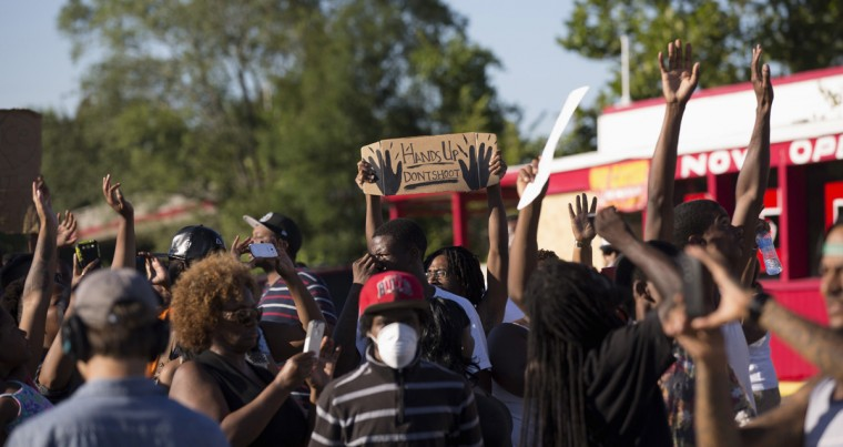Demonstrators raise their hands while protesting the shooting death of teenager Michael Brown, in Ferguson, Missouri August 13, 2014. Police in Ferguson fired several rounds of tear gas to disperse protesters late on Wednesday, on the fourth night of demonstrations over the fatal shooting last weekend of an unarmed black teenager Brown, 18, by a police officer on Saturday after what police said was a struggle with a gun in a police car. A witness in the case told local media that Brown had raised his arms to police to show that he was unarmed before being killed. (Mario Anzuoni/Reuters)