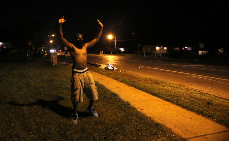 A demonstrator raises his hands in front of of a police officer in Ferguson, Missouri August 11, 2014. Police fired tear gas after rioting broke out for a second night in Ferguson, Missouri, despite calls on Monday for calm from the mother of a black teenager who was shot to death by police at the weekend. Michael Brown, 18, was shot to death in the mostly black St Louis suburb on Saturday afternoon after what police said was a struggle with a gun in a police car. (Mario Anzuoni /Reuters)