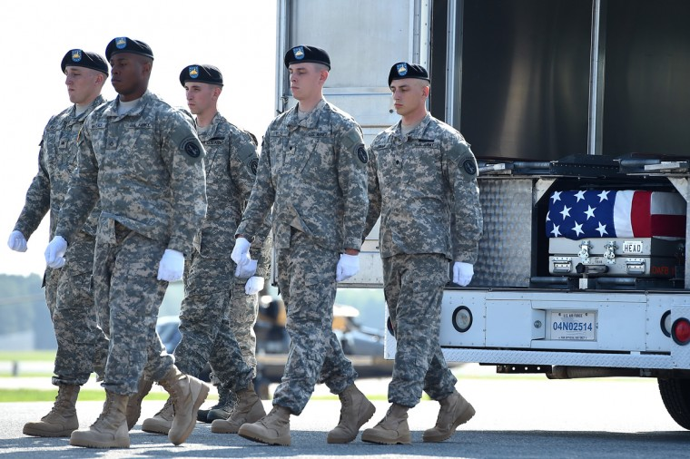 U.S. Army soldiers walk away from the transfer vehicle after carrying the flag-draped transfer case containing the remains of U.S. Army Maj. Gen. Harold J. Greene during a dignified transfer at Dover Air Force Base on August 7, 2014 in Dover, Delaware. According to reports, Greene, who was from Schenectady, New York, assigned to the Combined Security Transition Command, was killed after his unit was attacked in Afghanistan. (Photo by Patrick Smith/Getty Images)