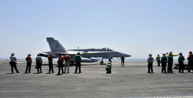 Sailors make final inspections on an F/A-18C Hornet assigned to the Golden Warriors of Strike Fighter Squadron (VFA) 87 aboard the aircraft carrier USS George H.W. Bush (CVN 77) in the Gulf, in this August 7, 2014 handout image released on August 8. Two F/A-18 aircraft conducted an airstrike on Friday against Islamic State artillery used against Kurdish forces defending the city of Arbil, near U.S. personnel, a Pentagon spokesman said. Picture taken August 7, 2014. (REUTERS/Mass Communication Specialist 3rd Class Margaret Keith/U.S. Navy/Handout via Reuters)