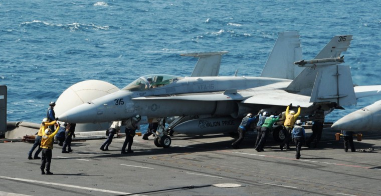 Sailors guide an F/A-18C Hornet assigned to the Valions of Strike Fighter Squadron (VFA) 15 on the flight deck of the aircraft carrier USS George H.W. Bush (CVN 77) in the Gulf, in this handout image taken and released on August 8, 2014. Two F/A-18 aircraft from the squadron conducted an airstrike on Friday against Islamic State artillery used against Kurdish forces defending the city of Arbil, near U.S. personnel, a Pentagon spokesman said. (REUTERS/Mass Communication Specialist 3rd Class Lorelei Vander Griend/U.S. Navy/Handout via Reuters)