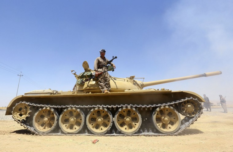 A member of the Kurdish peshmerga troops stands on a tank during an operation against Islamic State militants in Makhmur, on the outskirts of the province of Nineveh August 7, 2014. The United States began to drop relief supplies to beleaguered Yazidi refugees fleeing Islamist militants in Iraq, but there was no immediate sign on Friday of U.S. air strikes to halt the sweeping advance of Islamic State fighters. Picture taken August 7, 2014. (REUTERS/Stringer)