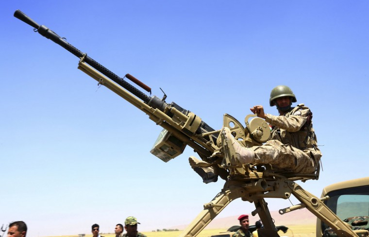 A member of the Kurdish peshmerga forces sit with a weapon during an intensive security deployment against Islamic State militants in Makhmur, on the outskirts of the province of Nineveh August 7, 2014. The United States began to drop relief supplies to beleaguered Yazidi refugees fleeing Islamist militants in Iraq, but there was no immediate sign on Friday of U.S. air strikes to halt the sweeping advance of Islamic State fighters. Picture taken August 7, 2014. (REUTERS/Stringer)
