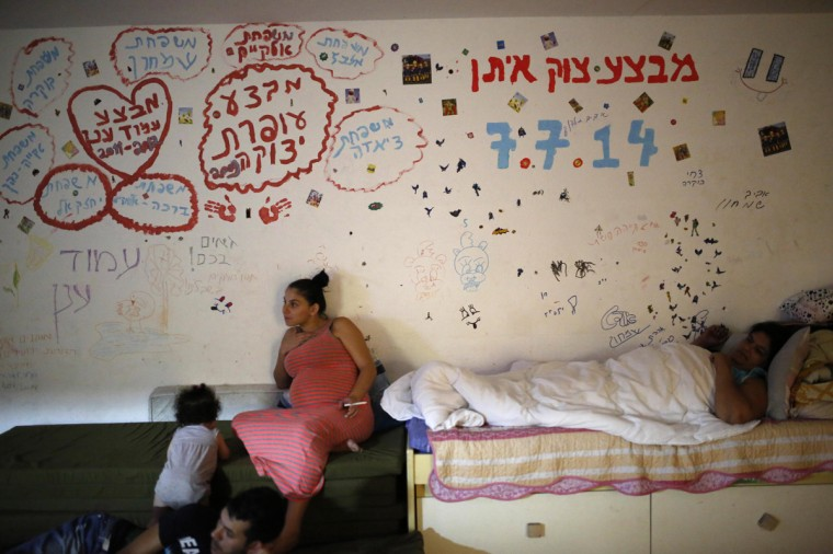 "Israelis are seen in a bomb shelter in the Israeli southern city of Ashkelon July 31, 2014. Israel declared a Gaza ceasefire over on Friday, saying Hamas militants breached the truce soon after it came in effect and apparently captured an Israeli officer while killing two other soldiers. The 72-hour break announced by U.S. Secretary of State John Kerry and U.N. Secretary-General Ban Ki-moon was the most ambitious attempt so far to end more than three weeks of fighting, and followed mounting international alarm over a rising Palestinian civilian death toll. The writings on the wall in Hebrew spells out the names of families and the names of the Israeli operations in the Gaza Strip ""Operation Protective Edge, Operation Pillar Defense, Operation Cast Lead"". Picture taken July 31, 2014. (Amir Cohen/Reutrs)"