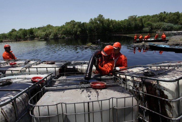 Workers pour oil into containers while trying to clean the river San Juan from leaked oil in Cadereyta August 22, 2014. (REUTERS/Daniel Becerril)