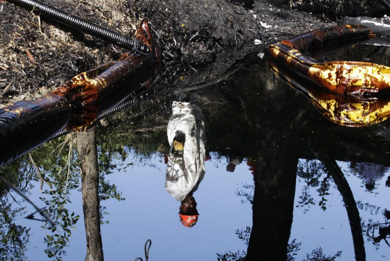The reflection of a worker is seen in leaked oil on the shores of the river San Juan in Cadereyta August 21, 2014. (REUTERS/Daniel Becerril)