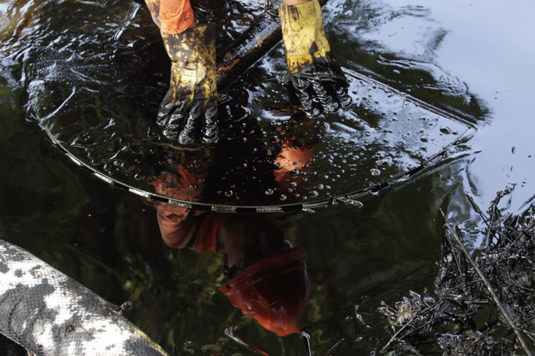 The reflection of a worker is seen in leaked oil as he tries to recover the oil from the shores of the river San Juan in Cadereyta August 21, 2014. (REUTERS/Daniel Becerril)