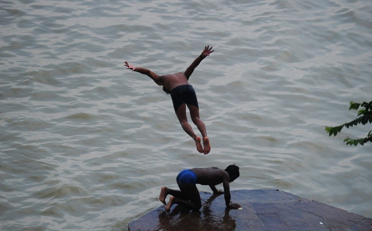 Indian youth jump into the flooded river Ganga as water levels of the River Ganga increase in Allahabad on August 11, 2014. Heavy rain in several areas of north India has caused rivers to reach the danger mark and flooding has occurred in various places. (Sanjay Kanojia/AFP/Getty Images