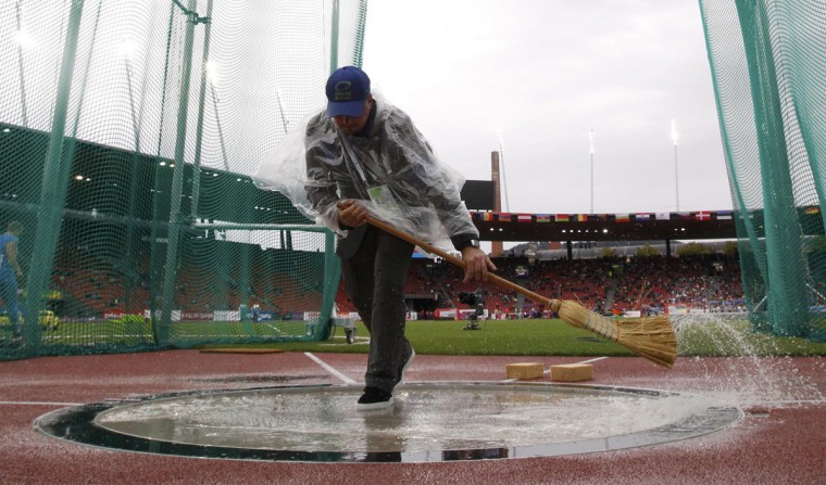 A worker clears rain water from the circle during the women's hammer throw at the European Athletics Championships at the Letzigrund Stadium in Zurich August 13, 2014. (Phil Noble/REUTERS)
