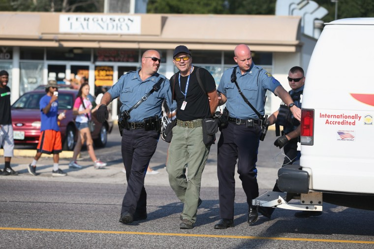 Getty Images staff photographer Scott Olson is placed into a paddy wagon after being arrested by police as he covers the demonstration following the shooting death of Michael Brown on August 18, 2014 in Ferguson, Missouri. Protesters have been vocal asking for justice in the shooting death of Michael Brown by a Ferguson police officer on August 9th. (Photo by Joe Raedle/Getty Images)