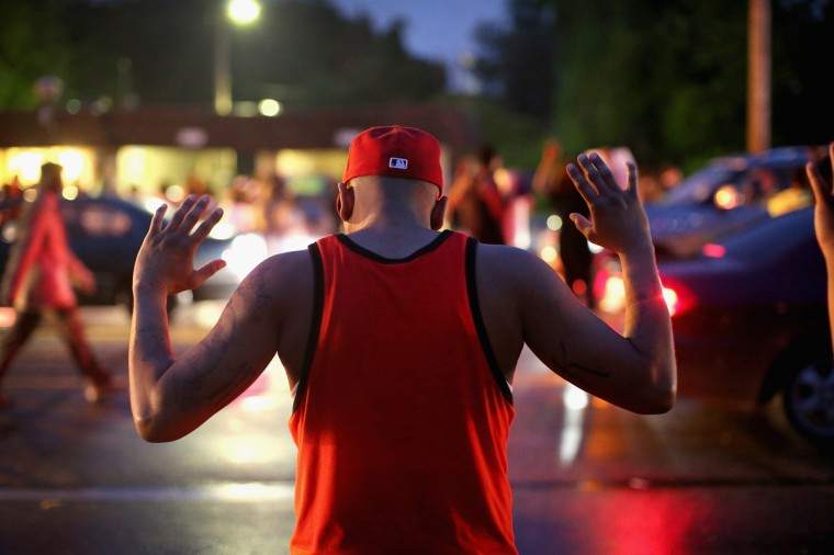 "Demonstrators gather along West Florissant Avenue to protest the shooting of Michael Brown on August 15, 2014 in Ferguson, Missouri. Brown was shot and killed by a Ferguson police officer on August 9. Protestors raise their hands and chant ""Hands up, don't shoot"" as a rally cry to draw attention to reports that stated Brown's hands were raised when he was shot. Tonight demonstration again ended with protestors clashing with police followed by more looting. (Photo by Scott Olson/Getty Images)"