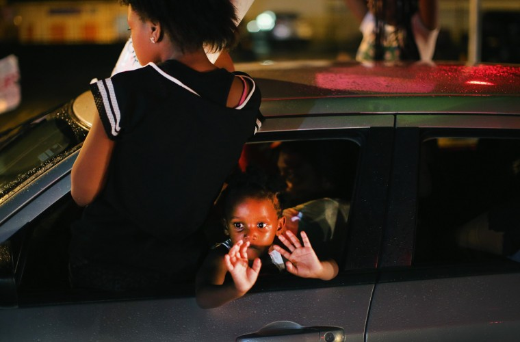 "A young child looks out from a car as demonstrators drive down West Florissant Avenue protesting the shooting and death of Michael Brown on August 15, 2014 in Ferguson, Missouri. Brown was shot and killed by a Ferguson police officer on August 9. Protestors raise their hands and chant ""Hands up, don't shoot"" as a rally cry to draw attention to reports that stated Brown's hands were raised when he was shot. Tonight demonstration again ended with protestors clashing with police followed by more looting. (Photo by Scott Olson/Getty Images)"