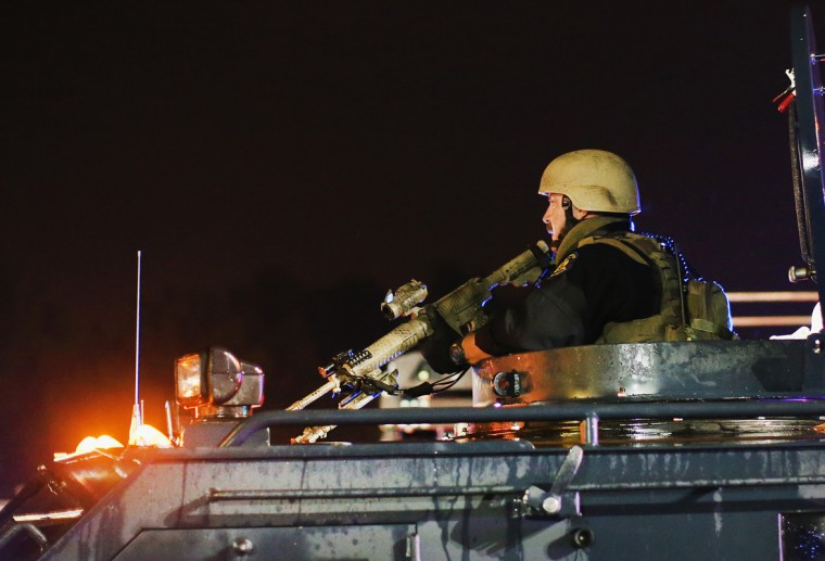 Police confront demonstrators during a protest over the shooting death of Michael Williams on August 15, 2014 in Ferguson, Missouri. Police shot pepper spray, smoke, gas and flash grenades at protestors before retreating. Several businesses were looted as the county police sat nearby with armored personnel carriers (APC). Violent outbreaks have taken place in Ferguson since the shooting death of Brown by a Ferguson police officer on August 9. (Photo by Scott Olson/Getty Images)