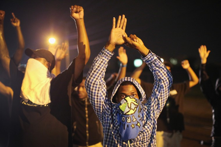 Demonstrators protesting the shooting death of Michael Williams confront police on August 15, 2014 in Ferguson, Missouri.Police shot pepper spray, smoke, gas and flash grenades at protestors before retreating. Several businesses were looted as police watched from their armored personnel carriers (APC) parked nearby. Violent outbreaks have taken place in Ferguson since the shooting death of Brown by a Ferguson police officer on August 9. (Photo by Scott Olson/Getty Images)