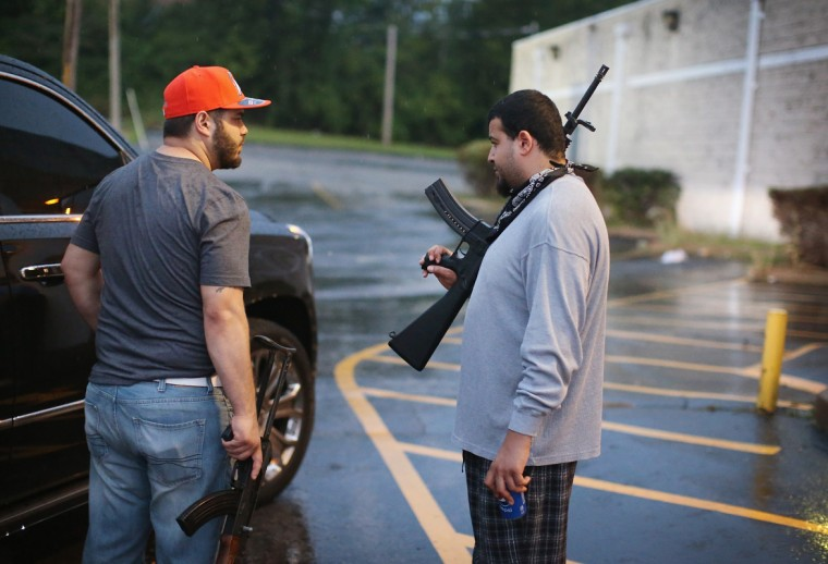 Business owners carry assault weapons to protect their grocery store after another night of rioting and looting following protests over the shooting death of Michael Brown on August 16, 2014 in Ferguson, Missouri. Looters ransacked several businesses for several hours as police held a position nearby with military grade weapons and armored personnel carriers (APC). Violent outbreaks have taken place almost nightly in Ferguson since the shooting death of Brown by a Ferguson police officer on August 9. (Photo by Scott Olson/Getty Images)
