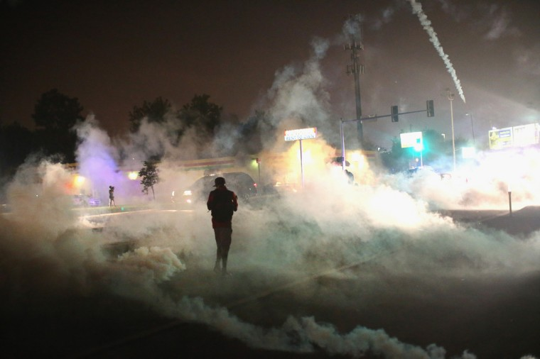 Tear gas fills the street as a demonstrator walks through the haze during protests over the killing of teenager Michael Brown by a Ferguson police officer, on August 17, 2014 in Ferguson, Missouri. Despite the Brown family's continued call for peaceful demonstrations, violent protests have erupted nearly every night in Ferguson since his August 9, death. (Photo by Scott Olson/Getty Images)