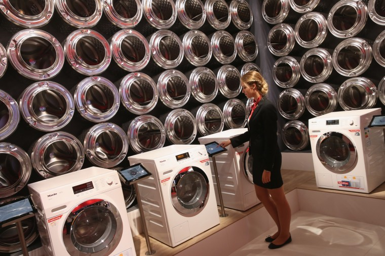A stand hostess checks the information tablet next to the latest generation of smart technology washing machines at the Miele stand at the 2014 IFA home electronics and appliances trade fair on September 5, 2014 in Berlin, Germany. IFA is the world's biggest fair of its kind and is open to the public through September 10. (Sean Gallup/Getty Images)