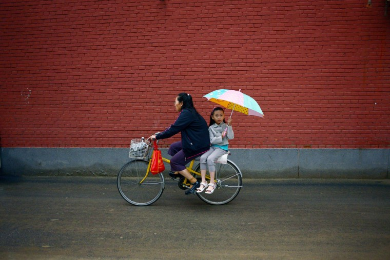 A girl holds an umbrella on the back of a bicycle along a road after school in Beijing on September 2, 2014. China tightens school security after a man stabbed three children and a teacher on September 1, state media said. (AFP PHOTO/Getty Images/Wang Zhao)