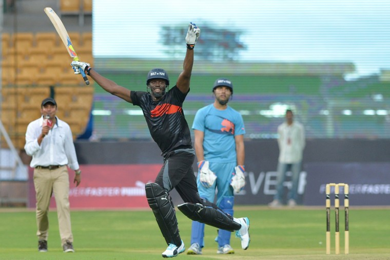 Jamaican Olympic Champion sprinter Usain Bolt (C) celebrates after his team won the four-over exhibition match against Indian cricketer Yuvraj Singh's team at Chinnaswamy Stadium in Bangalore on September 2, 2014. Bolt, on his first-ever visit to India, took part in an exhibition cricket match with some of India's top players. (AFP PHOTO/Getty Images/Manjunath Kiran)