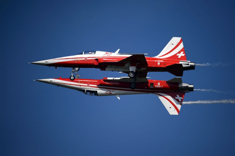 "Two fighter jets of the ""Patrouille Suisse"" (Swiss patrol) perform the ""mirror"" formation during the second week-end of the AIR14 air show on September 6, 2014 in Payerne, western Switzerland. (FABRICE COFFRINI/AFP/Getty Images)"
