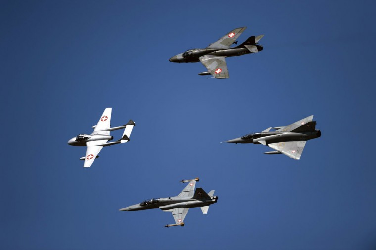 "Former fighter jets of the Swiss Air Force, the ""De Havilland Vampire"" (left), the ""Hawker Hunter"" (above), the ""Northrop F-5 Tiger"" (Bellow), and the ""Dassault Mirage III"" (right) perform during the second weekend of the AIR14 air show on September 6, 2014 in Payerne, western Switzerland. (FABRICE COFFRINI/AFP/Getty Images)"